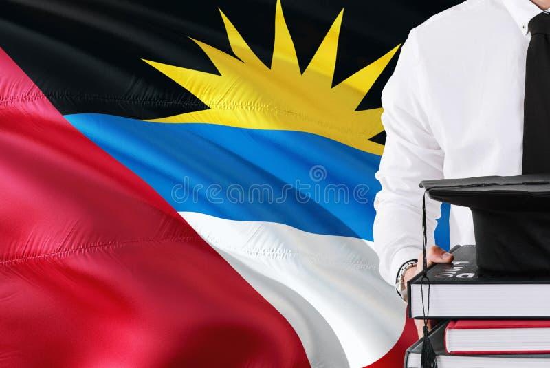 Lyckat studentutbildningsbegrepp Hållande böcker och avläggande av examenlock över Antigua och Barbudaflaggabakgrund royaltyfria foton