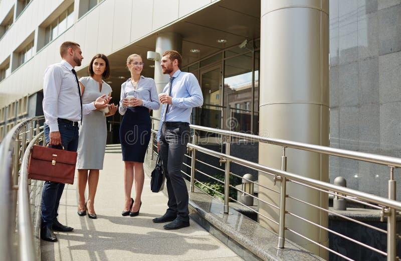 Lyckat ungt affärsfolk med kontorsbyggnad royaltyfria bilder
