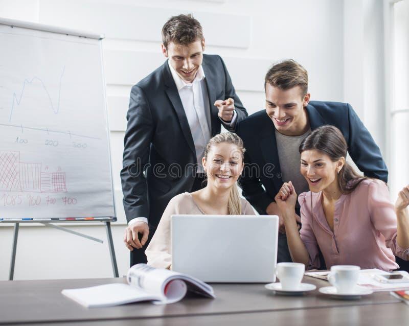 Lyckat ungt affärsfolk som använder bärbara datorn i möte royaltyfria foton