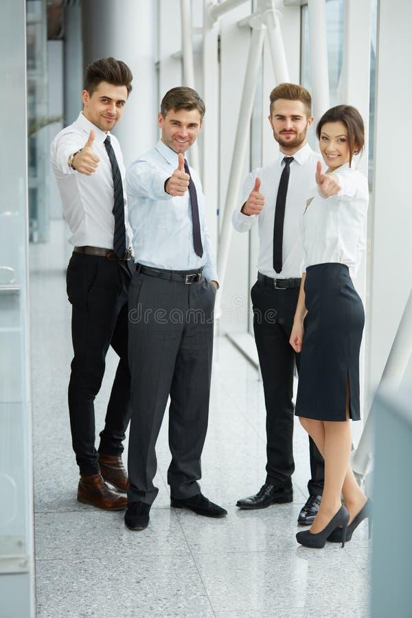 Lyckat ungt affärsfolk som visar tummar royaltyfri bild