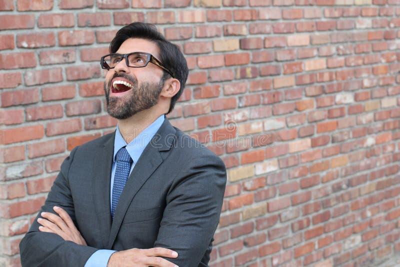 Lyckat upphetsat lyckligt leende för affärsman som upp till ser tomt kopieringsutrymme, stilig ung affärsmanöverraskning med kors arkivbilder