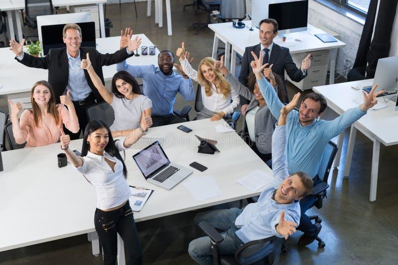 Lyckat upphetsat Team Sitting At Table On för blandningloppBusinesspeople som möte rymmer lyftt lycklig le affär för hand royaltyfri bild