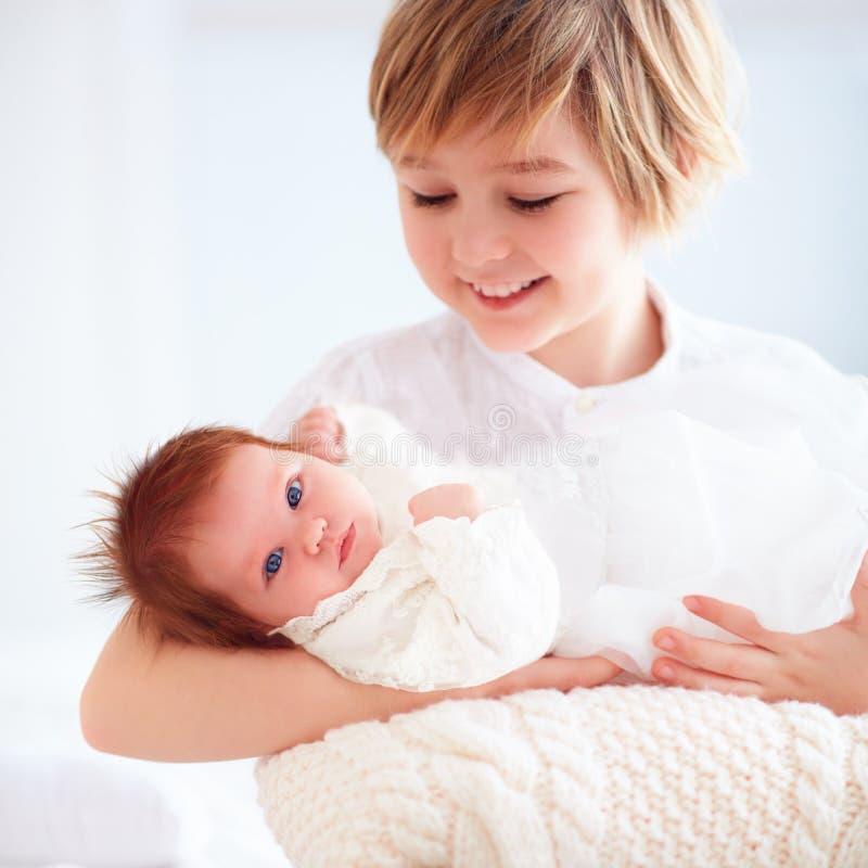 Lycklig äldre broder som rymmer hans nyfödda lilla syster royaltyfri bild