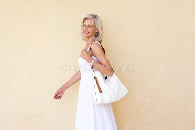 Lycklig äldre kvinna i sommarklänning som går med handväskan royaltyfri bild