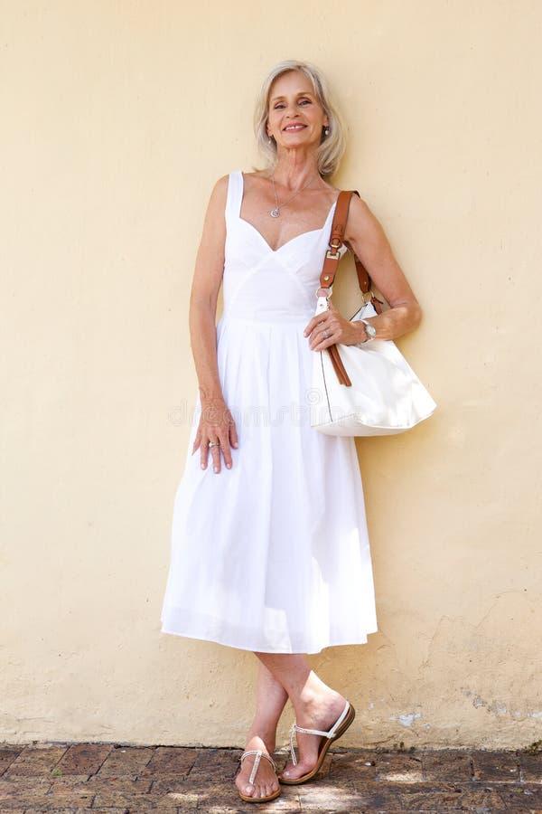 Lycklig äldre kvinna i vårklänninganseende med handväskan arkivfoto