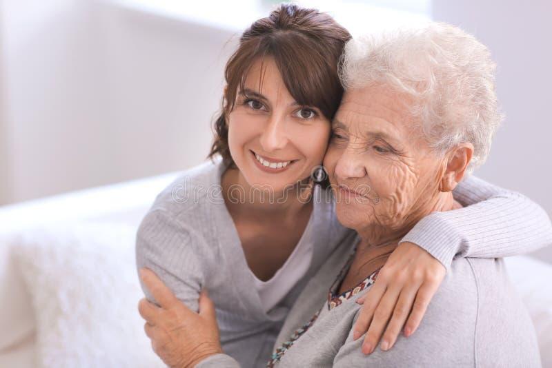 Lycklig äldre kvinna med hennes dotter hemma royaltyfri fotografi