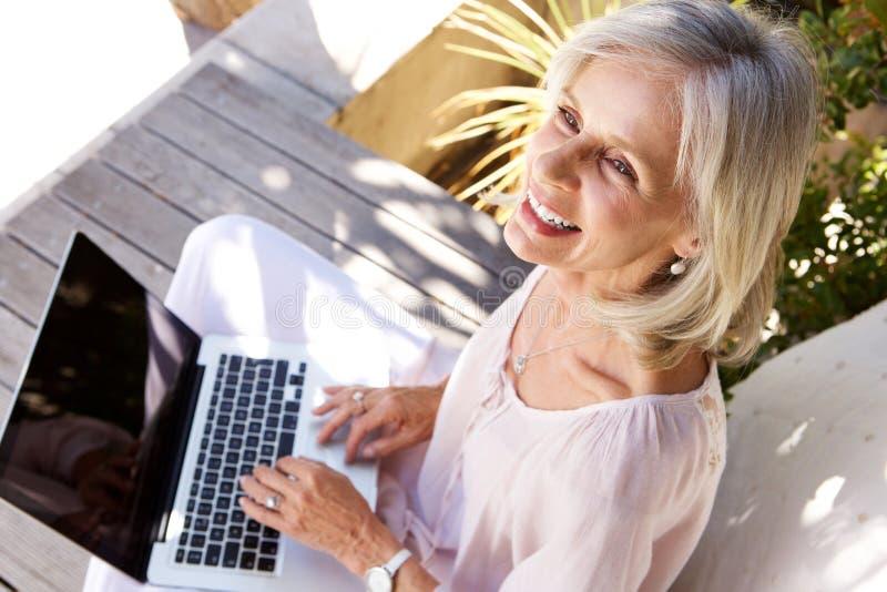 Lycklig äldre kvinna med sammanträde för bärbar datordator utanför royaltyfri fotografi