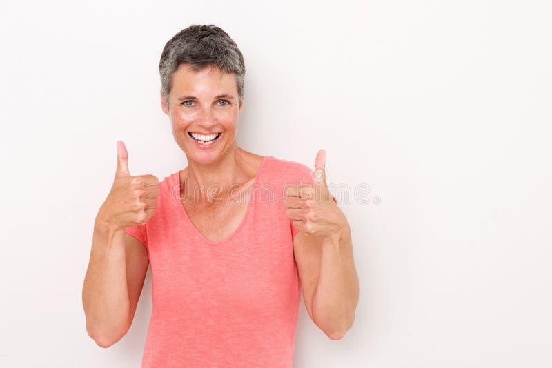 Lycklig äldre kvinna med tummar upp mot vit bakgrund arkivbild