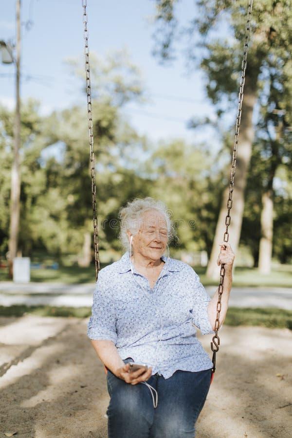 Lycklig äldre kvinna på en gunga royaltyfria bilder