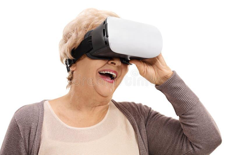 Lycklig äldre kvinna som använder en VR-hörlurar med mikrofon arkivbild