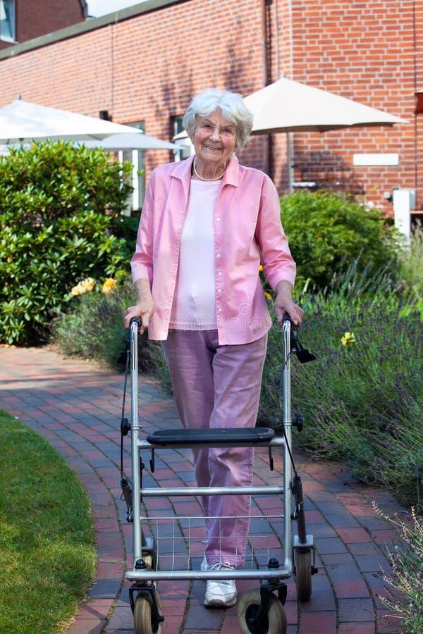Lycklig äldre kvinna som använder ett gå hjälpmedel arkivfoton