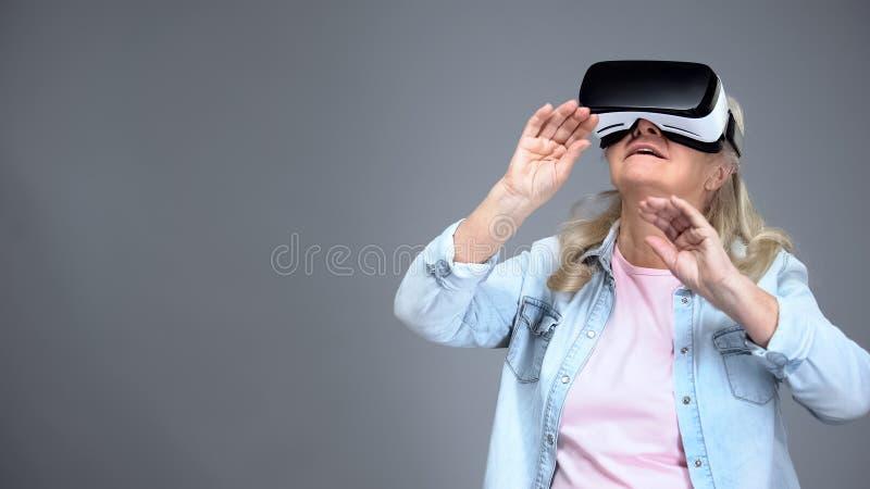 Lycklig äldre kvinna som bär VR-hörlurar med mikrofon som spelar lekar, innovativa teknologier royaltyfria bilder
