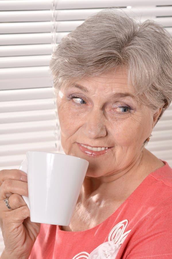 Lycklig äldre kvinna som dricker te på vit bakgrund för fönsterrullgardiner royaltyfria foton