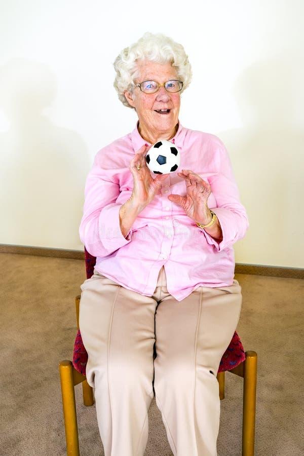 Lycklig äldre kvinna som fångar en boll arkivfoton