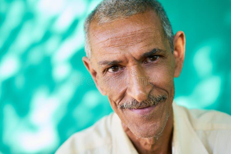 Lycklig äldre latinamerikansk man för folkstående som ler på kameran royaltyfria bilder