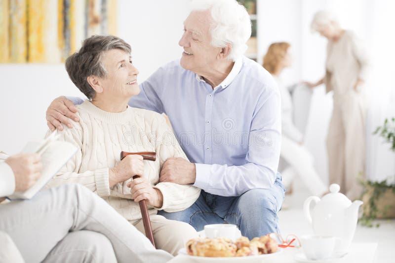 Lycklig äldre man som kramar frun fotografering för bildbyråer