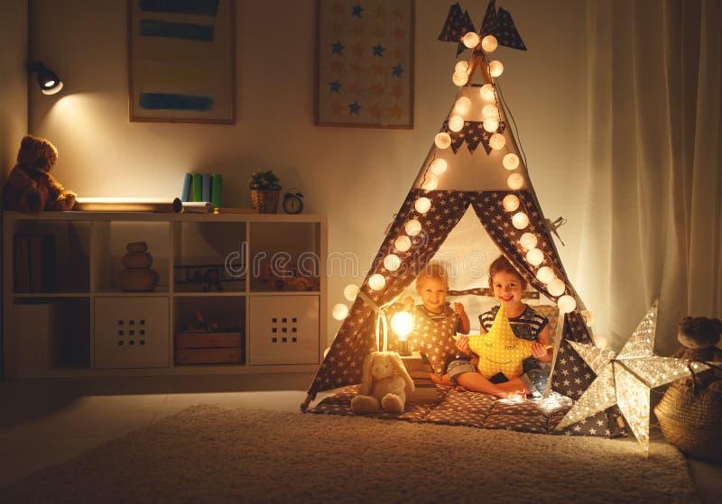 Lycklig älska barnsyskongrupplek i mörkt tält i lekrum hemma arkivbilder