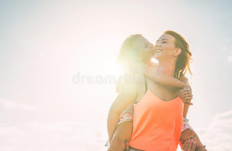 Lycklig älska familjdotter som kysser hennes moder som har ett mjukt ögonblick på sommardagen - ung röd hårmamma som bär hennes u royaltyfria foton