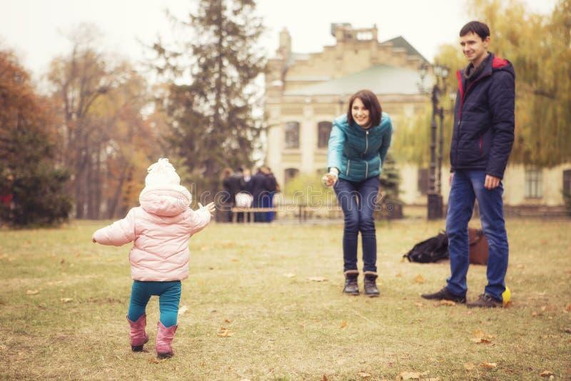 Lycklig älska family& x28; moder, fader och liten dotterkid& x29; outd royaltyfria bilder