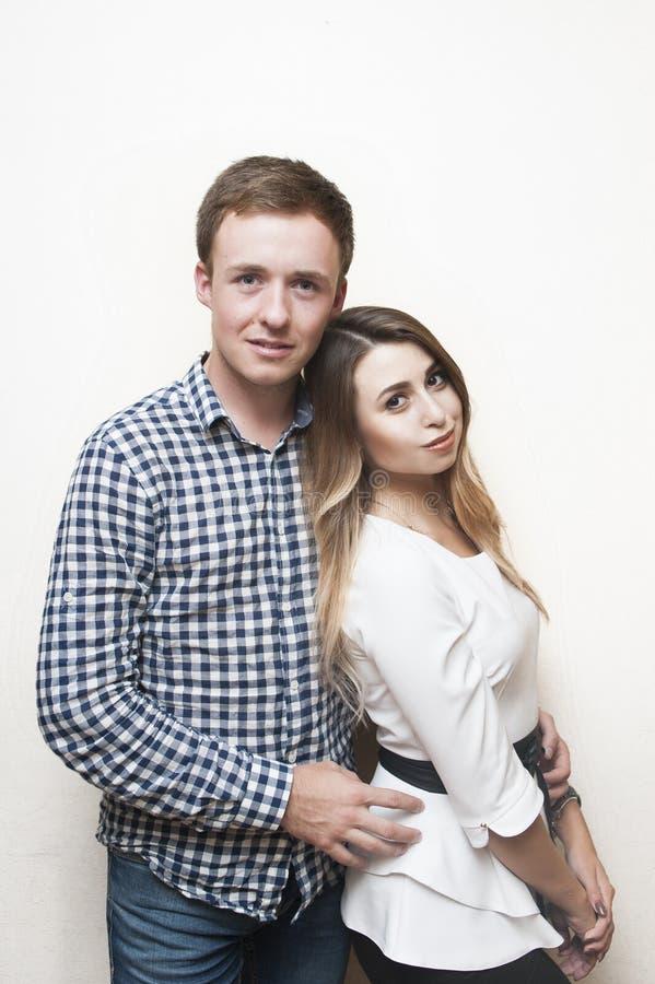 Lycklig älska grabb med en flicka på en ljus bakgrund royaltyfria bilder