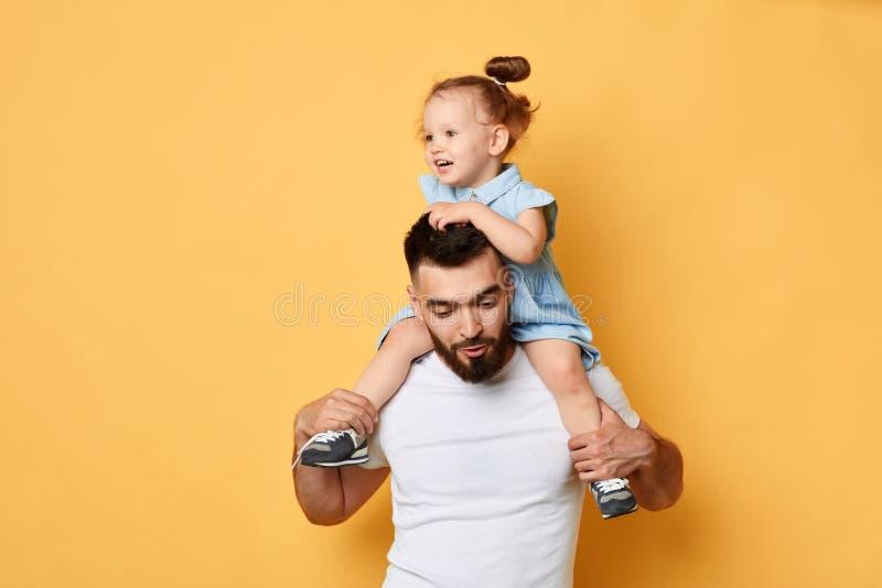 Lycklig älskvärd flicka i stilfull klänning som rider en pappa som en häst fotografering för bildbyråer