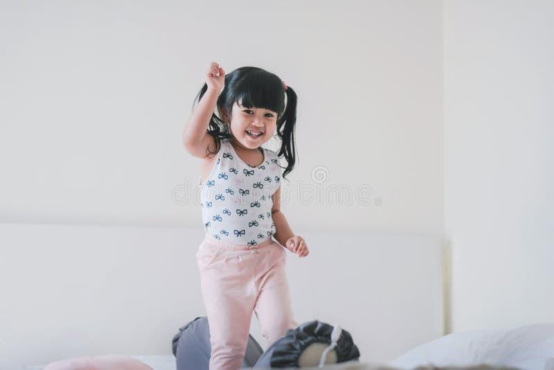 Lycklig älskvärd ungestående Tre år en gammal flicka i lyckaögonblick i sovrum royaltyfria bilder