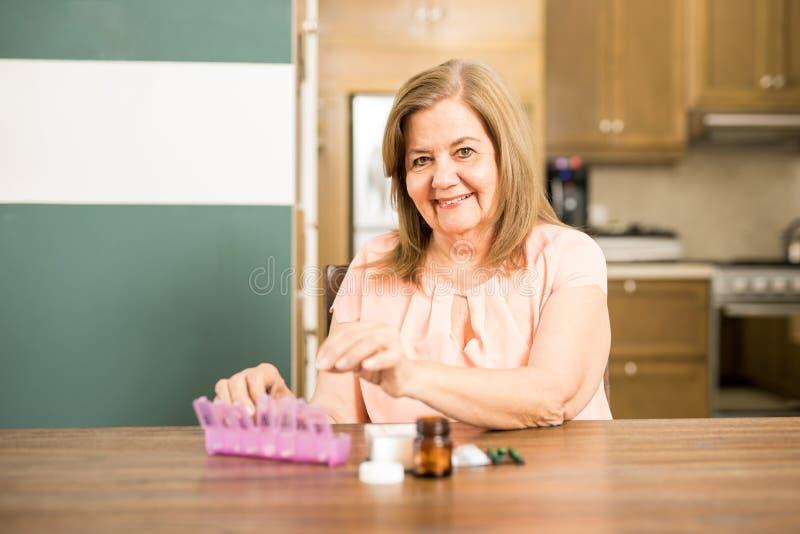 Lycklig åldrig kvinna som fyller hennes preventivpillerask fotografering för bildbyråer
