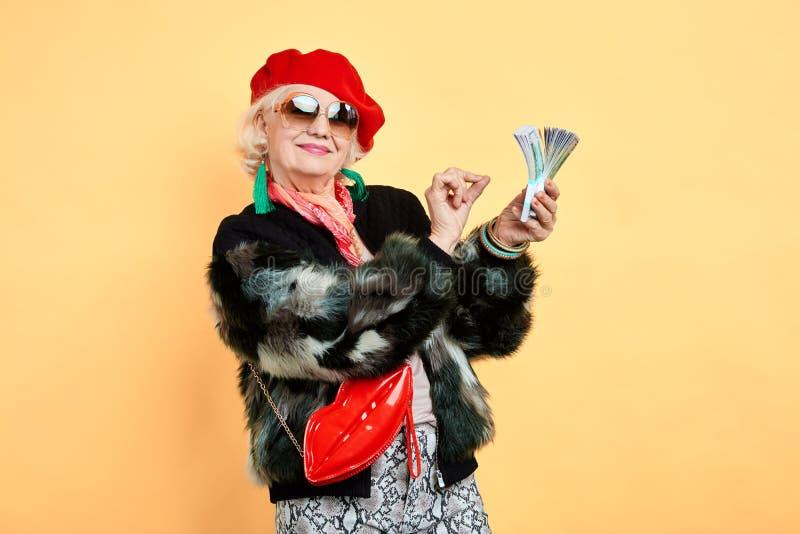Lycklig åldrig kvinna som rymmer pengar som räknar det, sinnesrörelse- och känslabegrepp arkivbilder