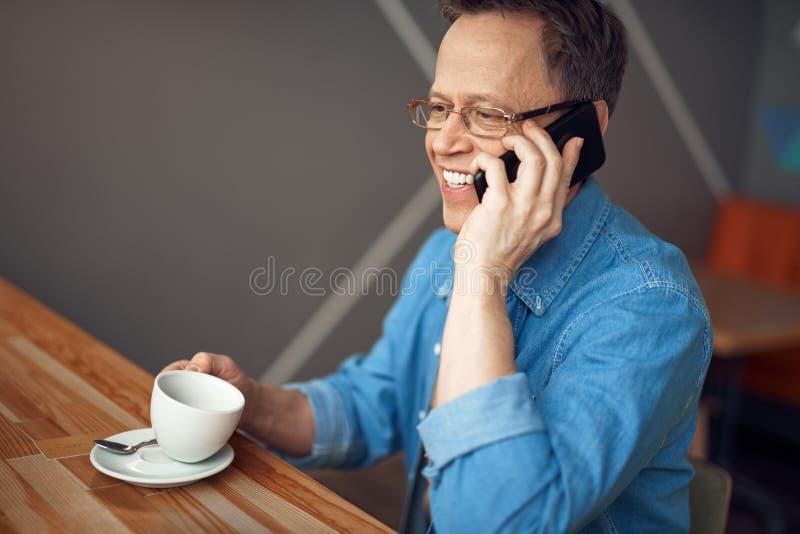 Lycklig åldrig man som talar vid mobiltelefonen i kafé arkivfoton