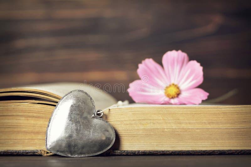 lycklig årsdag Hjärtahänge, tappningbok och blomma royaltyfri fotografi
