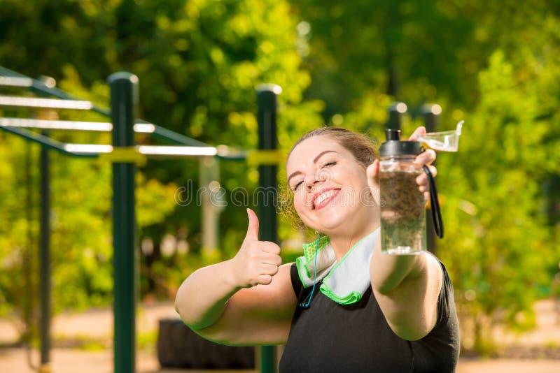 Lycklig överdimensionerad kvinna med flaskan av vattenleenden royaltyfri bild