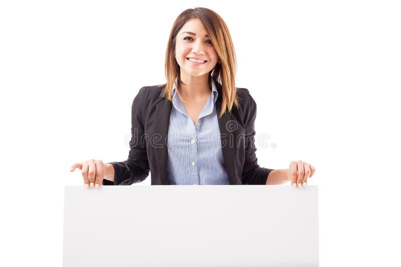 Lycklig affärsbiträde som rymmer ett tecken royaltyfri foto