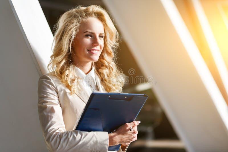 Lycklig affärsdam med härliga dokument och att le för hårinnehav fotografering för bildbyråer