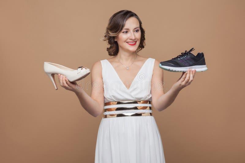 Lycklig affärskvinna i den vit klänningen och innehavgymnastikskor och hee royaltyfri foto