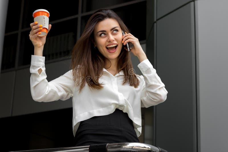 Lycklig affärskvinna i en skjorta som rymmer en kopp kaffe och talar på telefonen arkivfoto