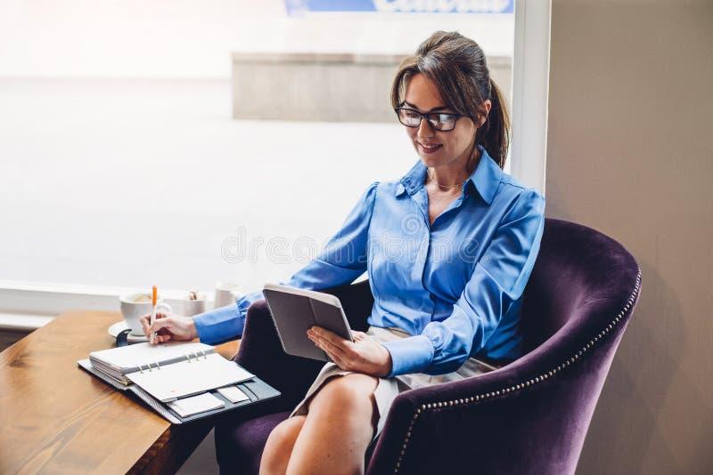 Lycklig affärskvinna i ett kafé arkivfoton