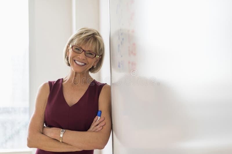 Lycklig affärskvinna Leaning On Whiteboard arkivbild