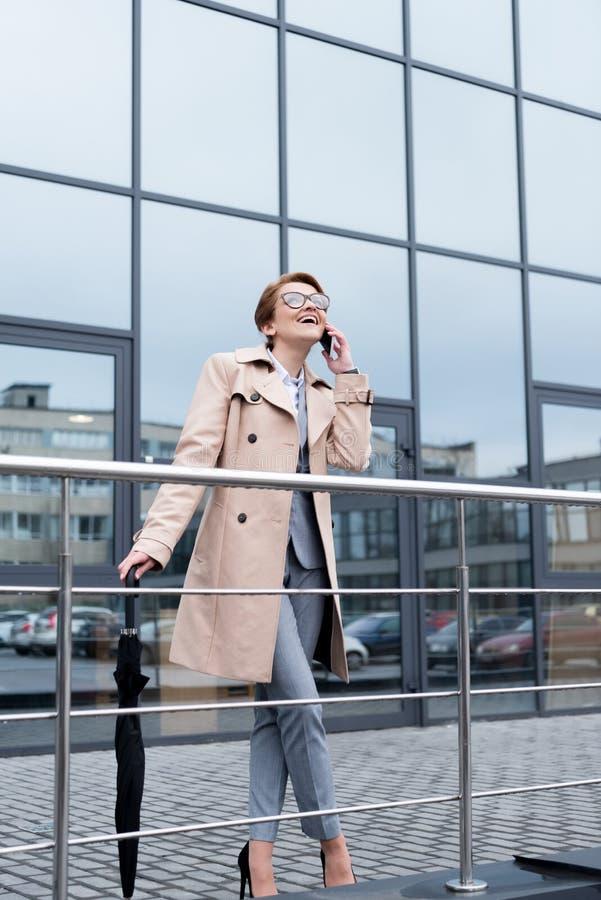 lycklig affärskvinna med paraplyet som talar på smartphonen arkivfoton
