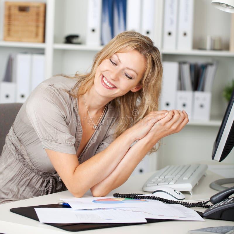 Lycklig affärskvinna Sitting At Desk arkivbilder
