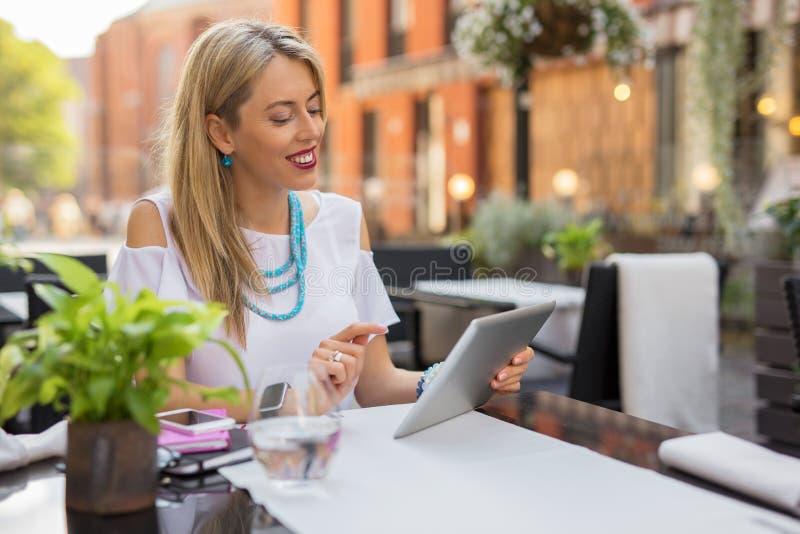 Lycklig affärskvinna som använder minnestavlan fotografering för bildbyråer
