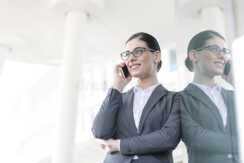 Lycklig affärskvinna som använder mobiltelefonen, medan luta på glasväggen royaltyfria foton