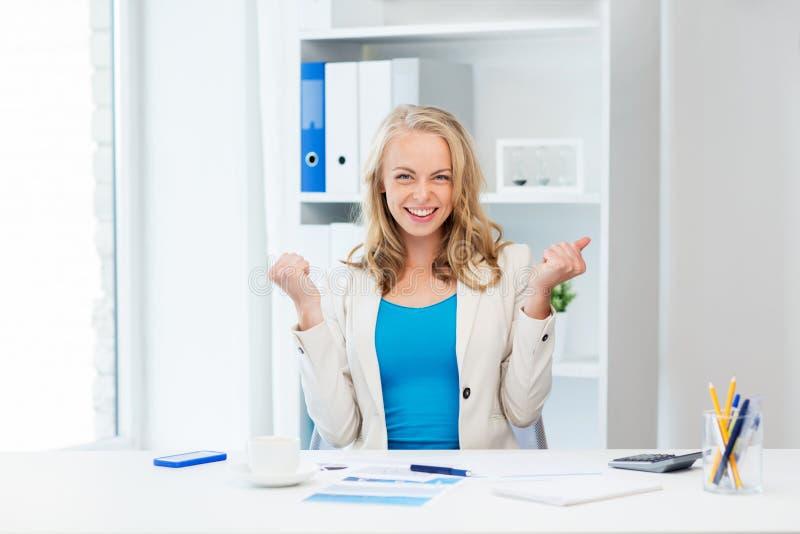 Lycklig affärskvinna som firar framgång på kontoret arkivfoton