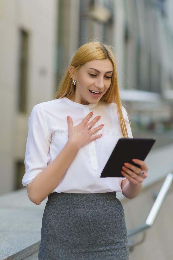 Lycklig affärskvinna som framme använder minnestavlaPC av kontorsbyggnad fotografering för bildbyråer