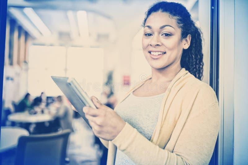Lycklig affärskvinna som i regeringsställning använder den digitala kafeterian för minnestavla arkivbilder
