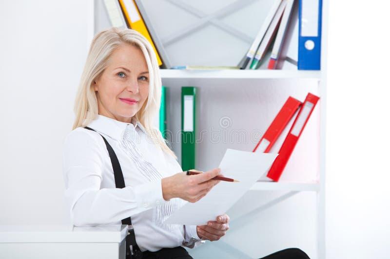Lycklig affärskvinna som i regeringsställning arbetar med dokument royaltyfri fotografi
