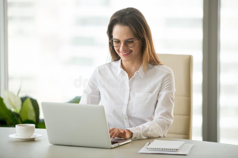 Lycklig affärskvinna som ler att prata med vänner på bärbara datorn arkivbild