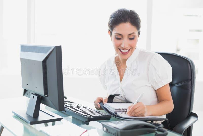 Lycklig affärskvinna som ordnar hennes dagordning på hennes skrivbord royaltyfria bilder