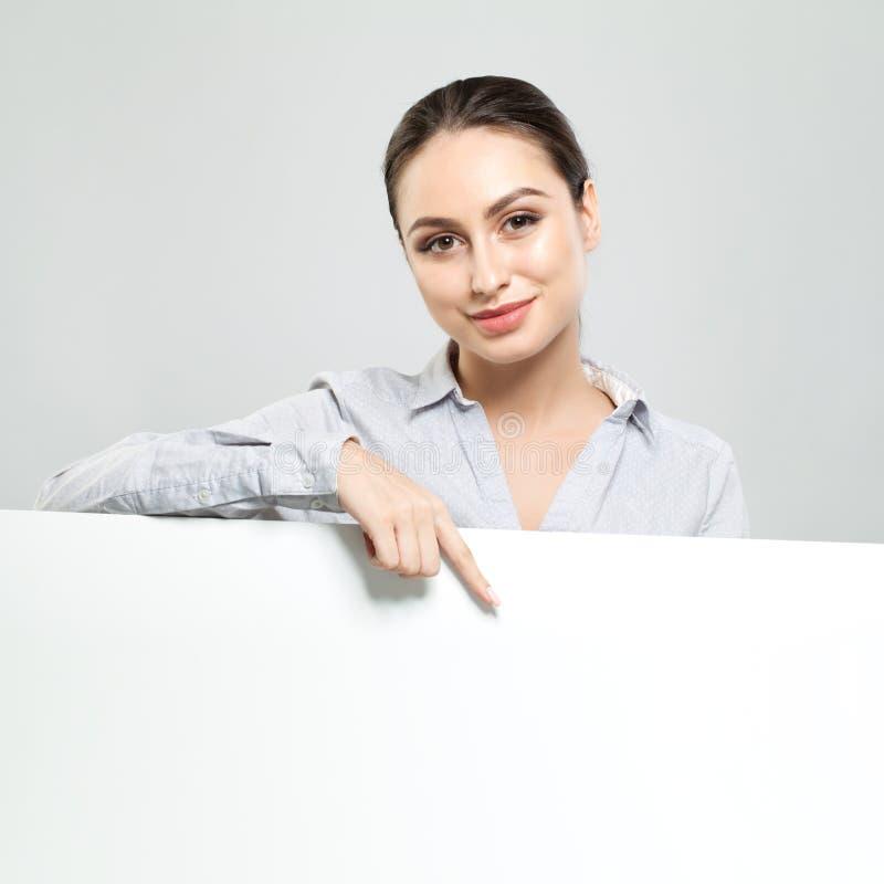 Lycklig affärskvinna som pekar och rymmer vit tom skyltbakgrund Ungt kvinnabegrepp för le, affärs- och utbildnings royaltyfri foto