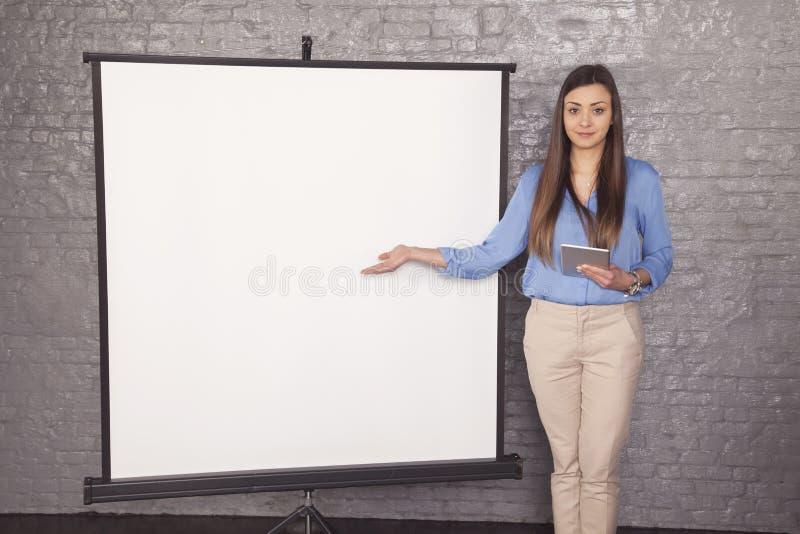 Lycklig affärskvinna som pekar till ett ställe på brädet, kopieringsspac royaltyfria foton