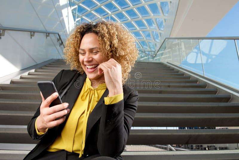 Lycklig affärskvinna som sitter på trappa som ser mobiltelefonen arkivbilder